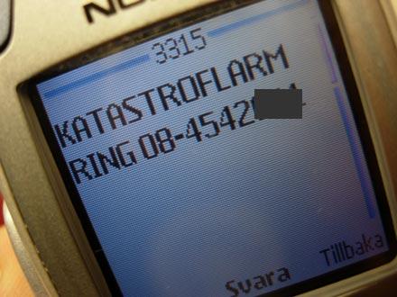 På mobiltelefonens skärm syns texten KATASTROFLARM - RING och därefter ett nummer
